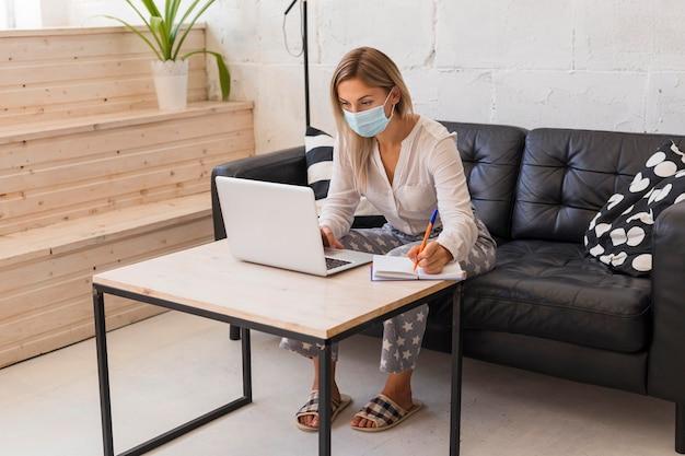 Pełny strzał kobieta z maską i laptopem