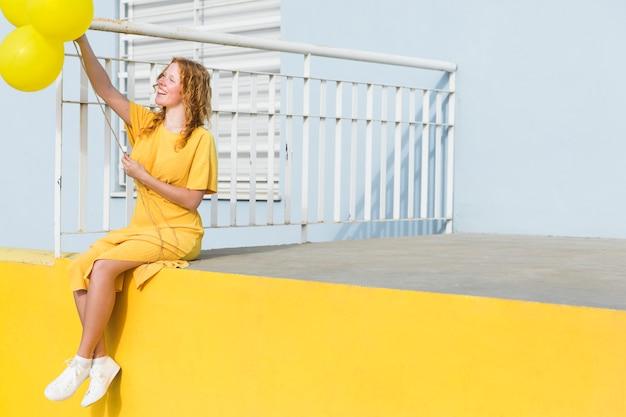 Pełny strzał kobiety koloru żółtego balony
