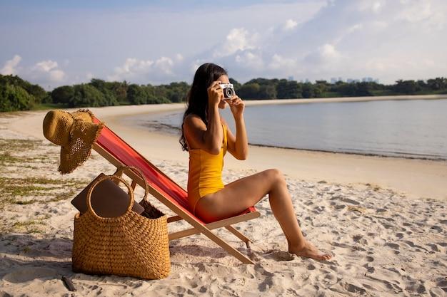 Pełny strzał kobiety na plaży robiący zdjęcia