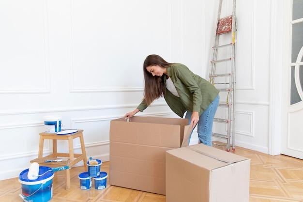 Pełny strzał kobiety otwierającej pudełko w domu