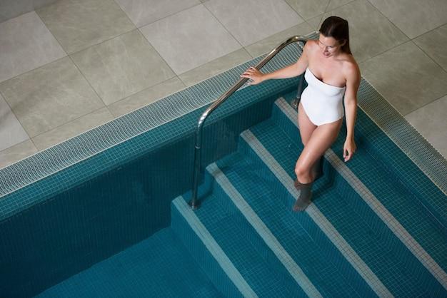 Pełny strzał kobiety przy basenie pod dużym kątem