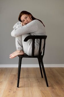 Pełny strzał kobiety siedzącej na krześle