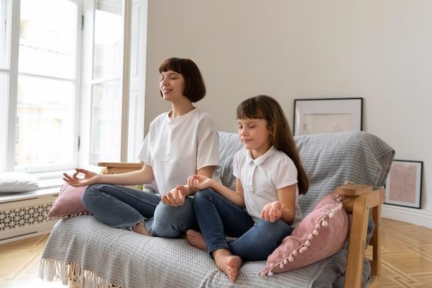 Pełny strzał matka i dziewczyna medytująca na kanapie