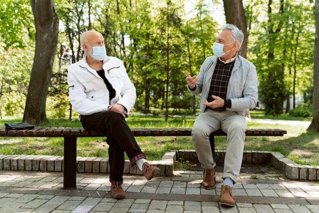Pełny strzał mężczyzn noszących maski na twarz