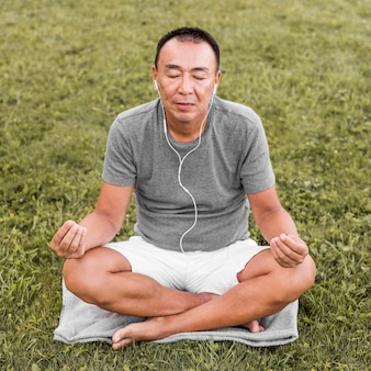 Pełny strzał mężczyzna medytuje na trawie