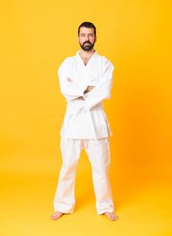 Pełny strzał mężczyzna nad odosobnionym żółtym tłem robi karate utrzymuje ręki krzyżować