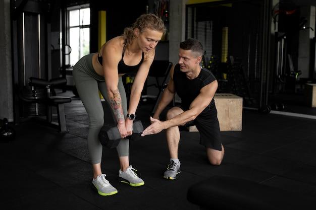 Pełny strzał mężczyzna pomagający kobiecie na siłowni