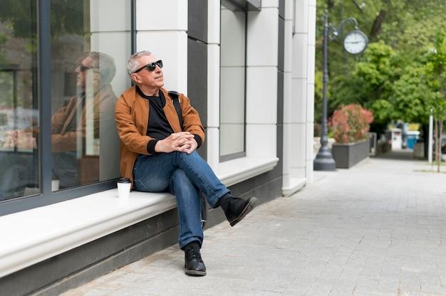 Pełny strzał mężczyzna siedzący na zewnątrz
