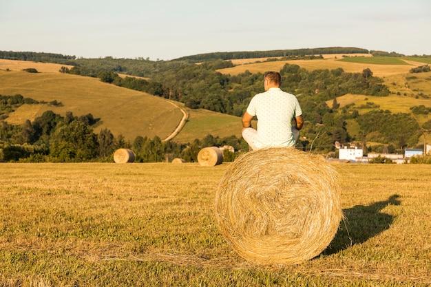 Pełny strzał mężczyzna siedzi na rolce siano