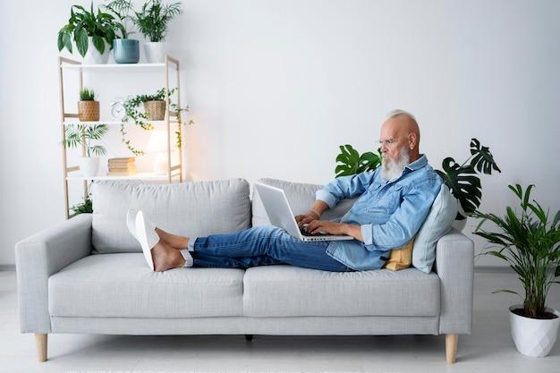 Pełny strzał mężczyzna studiujący na kanapie