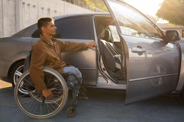 Pełny strzał mężczyzny na wózku inwalidzkim w pobliżu samochodu?