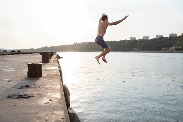 Pełny strzał mężczyzny skaczący w wodzie