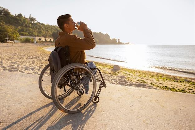 Pełny strzał mężczyzny w piciu na wózku inwalidzkim?