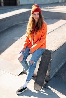 Pełny strzał młoda dziewczyna siedzi z skate