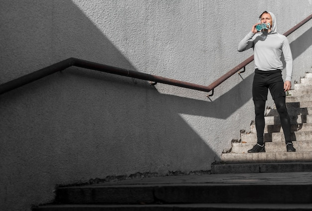 Pełny strzał młodego człowieka woda pitna na schodkach