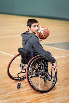 Pełny strzał młody niepełnosprawny mężczyzna trzyma piłkę