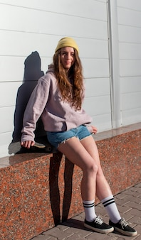Pełny strzał nastolatka siedzi na zewnątrz