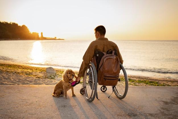 Pełny strzał niepełnosprawny mężczyzna podróżujący z psem