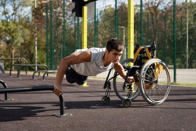 Pełny strzał niepełnosprawny mężczyzna robi pompki