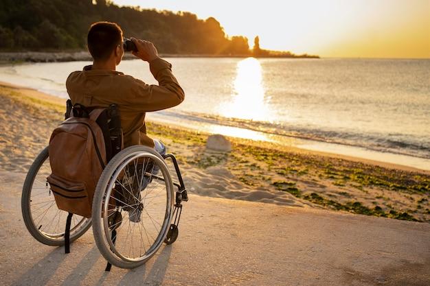Pełny strzał niepełnosprawny mężczyzna z lornetką