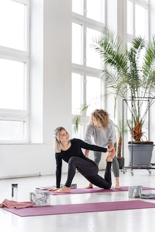 Pełny strzał praktyka jogi kobieta na macie