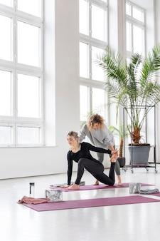 Pełny strzał praktyka jogi kobieta z nauczycielem