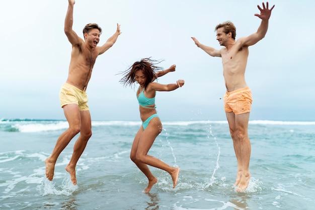 Pełny strzał przyjaciół skaczących w morzu