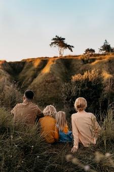 Pełny strzał słodkiej rodziny siedzącej na trawie