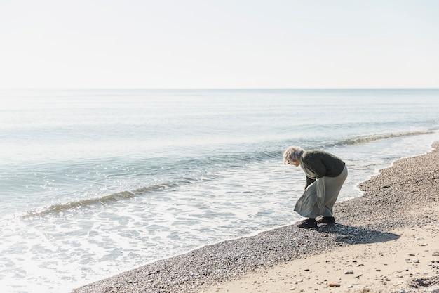 Pełny strzał stara kobieta blisko morza