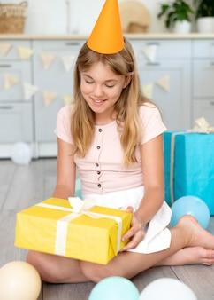 Pełny strzał szczęśliwa dziewczyna trzyma prezent