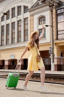 Pełny strzał szczęśliwa kobieta niesie bagaż