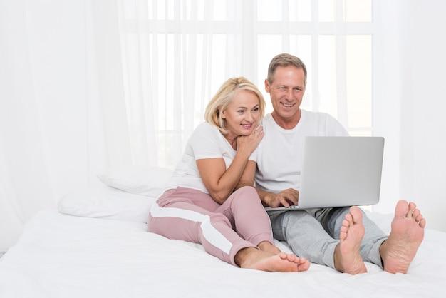 Pełny strzał szczęśliwa para z laptopem w sypialni