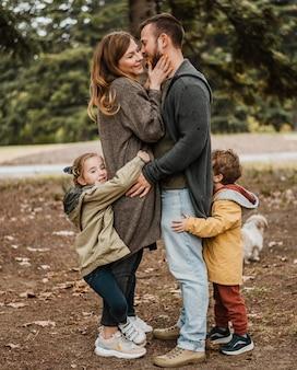 Pełny strzał szczęśliwa rodzina przytulanie