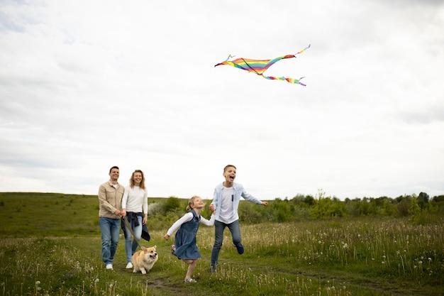Pełny strzał szczęśliwej rodziny latający latawiec