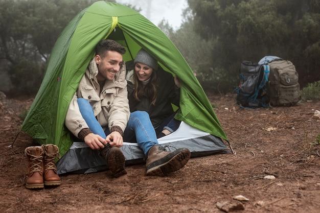 Pełny strzał szczęśliwi ludzie w zielonym namiocie