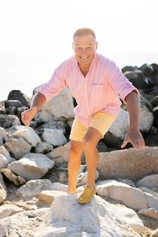 Pełny strzał szczęśliwy człowiek na skałach