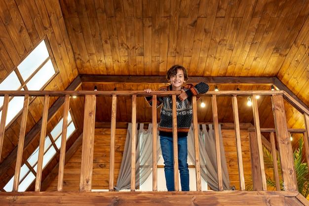 Pełny strzał szczęśliwy dzieciak pozuje blisko balustrady