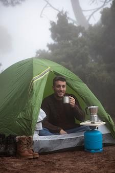 Pełny strzał szczęśliwy mężczyzna w namiocie