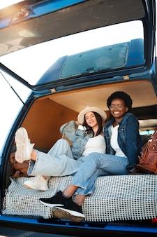 Pełny strzał szczęśliwych kobiet w furgonetce