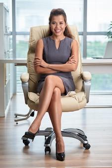 Pełny strzał ufnej damy siedząca noga nad nogą w biurowym krześle z rękami składać