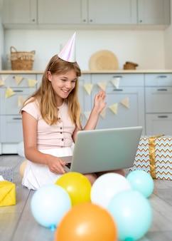 Pełny strzał urodzinowej dziewczyny trzymającej laptopa