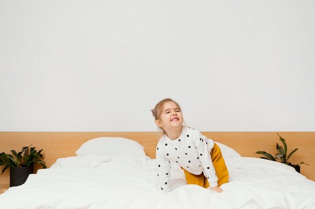 Pełny strzał uśmiechnięta dziewczyna stojąca na łóżku
