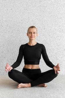 Pełny strzał uśmiechnięta kobieta siedzi w pozie jogi