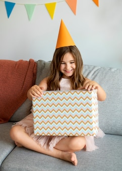 Pełny strzał uśmiechniętej dziewczyny otwierającej prezent na kanapie