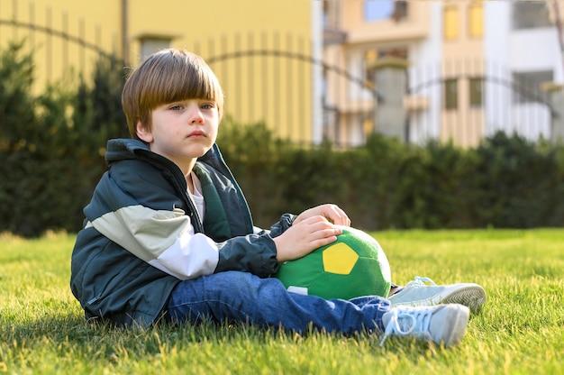 Pełny strzału dzieciaka obsiadanie na trawie