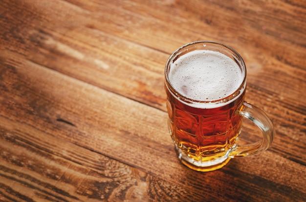 Pełny szkło piwo lager na drewnianym nieociosanym tle.