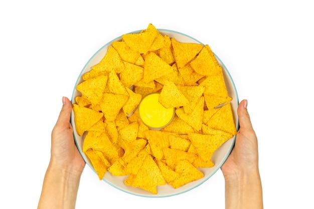 Pełny talerz chipsów kukurydzianych tortilli z sosem serowym w kobiecych rękach na białym talerzu widok z góry