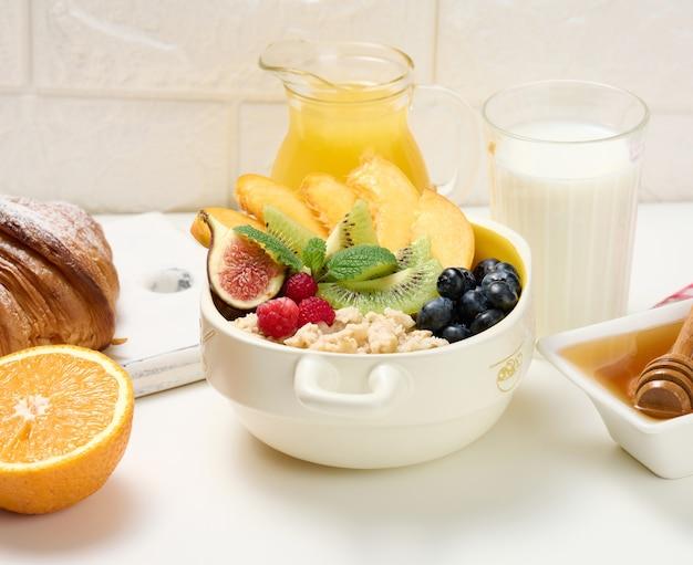 Pełny talerz z płatkami owsianymi i owocami, pół dojrzałej pomarańczy i świeżo wyciśnięty sok w przezroczystej szklanej karafce, miód w misce na białym stole. zdrowe śniadanie