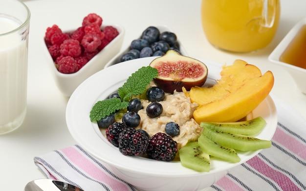 Pełny talerz z płatkami owsianymi i owocami, świeżo wyciśnięty sok w przezroczystej szklanej karafce. zdrowe śniadanie