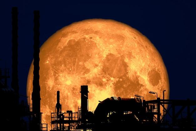 Pełny truskawkowy księżyc z powrotem na rafinerii sylwetki na nocnym niebie